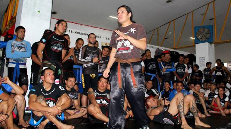 Trainer in Boxhalle spricht vor Box-Schülern