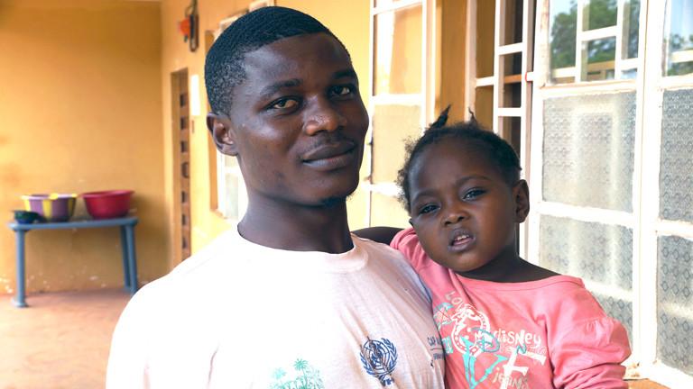 Ein Ebola-Überlebender kümmert sich um ein kleines Mädchen, bei dem Verdacht auf eine Ebola-Infektion besteht.