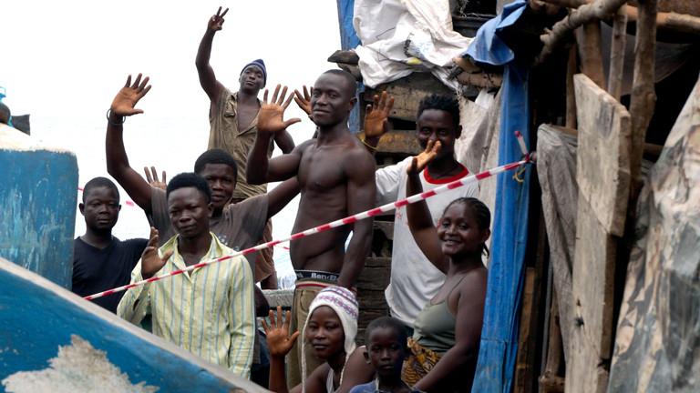 In einem Slum in Freetown wird eine Gasse mit einem Band abgesperrt. Die Menschen stehen unter Quarantäne.