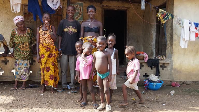 Eine Familie steht in dem Dorf Kallia vor ihrer Hütte.