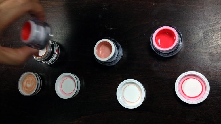 Dena begutachtet die verschiedenen Trendfarben wie Koralle und Rosé im Nagelstudio von Alex Schneider.