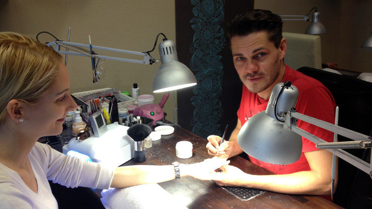 Der Nageldesigner Alex Schneider in seinem Studio mit einer Kundin
