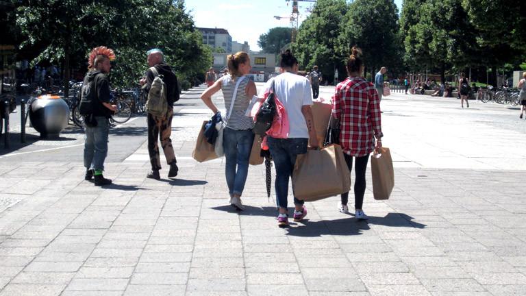 Punks in der Nähe des Alexanderplatzes, daneben Mädchen voll bepackt mit Primark-Tüten