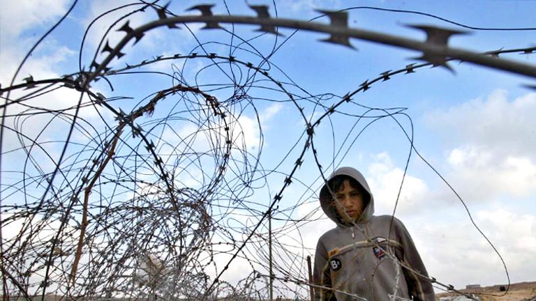 Ein Junge in einem Geflecht aus Natodrähten. Aufgenommen im Sperrgebiet des Gazastreifens 2006.