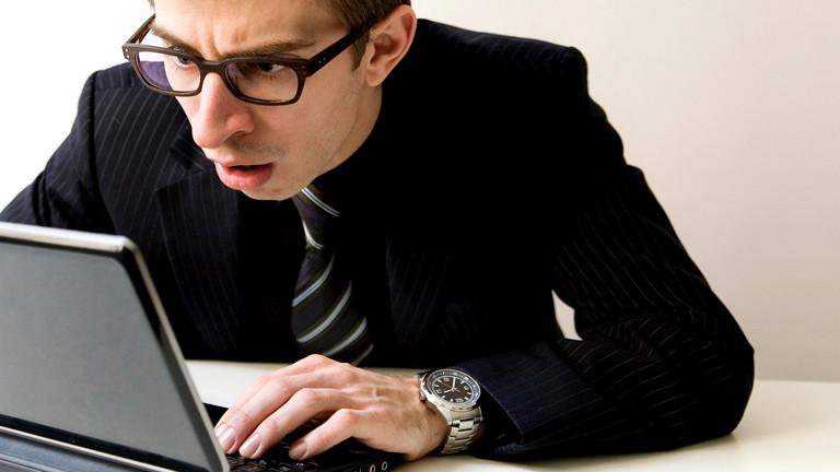 Ein Mann guckt schockiert auf seinen Laptop