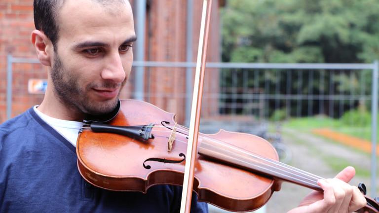 Omar spielt auf einer Geige im Heim in Brandenburg