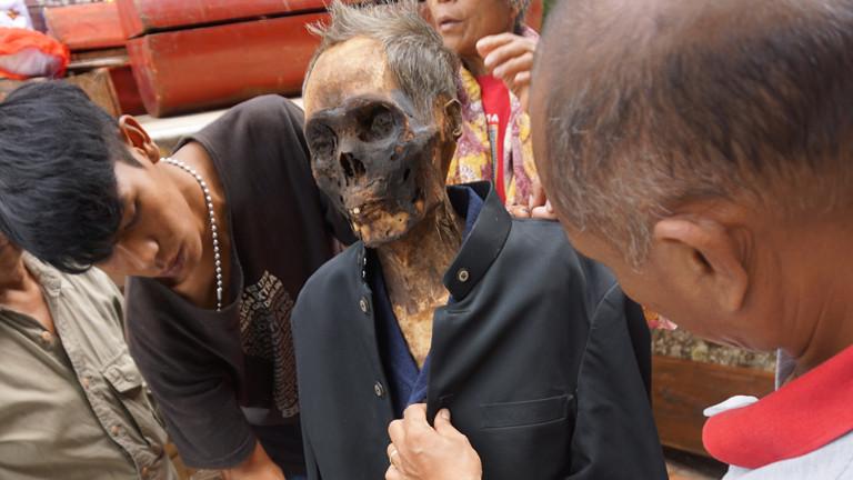 Angehörige haben einen Toten aus dem Sarg geholt und kleiden ihn neu ein.