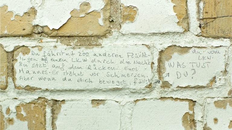 Rissige Wand mit einer darauf gekritzelten Geschichte einer Flucht.
