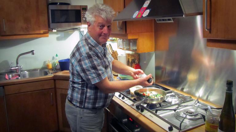 Conrad Böhlke schwenkt Grünkohl in der Pfanne mit Tomaten und Pinienkernen.