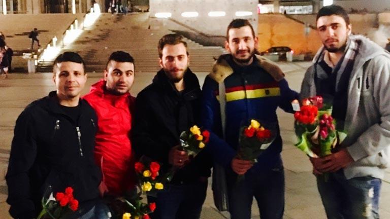Syrische Flüchtlinge verteilen Rosen am Kölner Hauptbahnhof