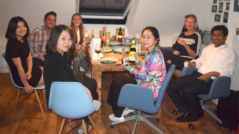 An einem Tisch sitzen acht Männer und Frauen. Auf dem Tisch stehen Teller, Gläser und Essen.