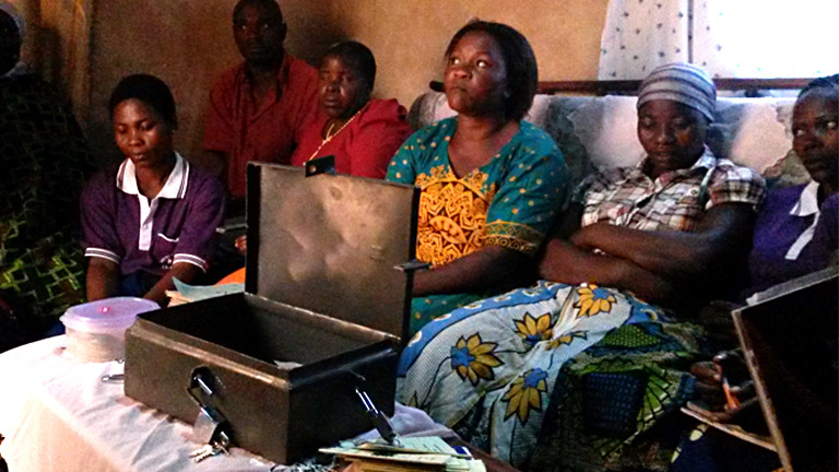 Frauen mit einer Eisentruhe in Tansania.