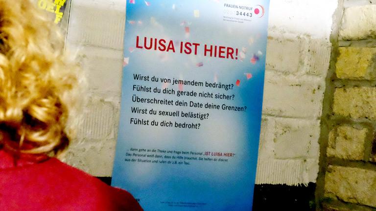 """In einer Kneipe hängt ein Plakat der Kampagne """"Luisa hier"""""""
