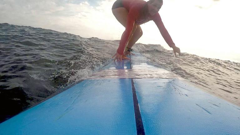Caro probiert Surfen aus. Ihr Lieblingssport aus diesem Monat