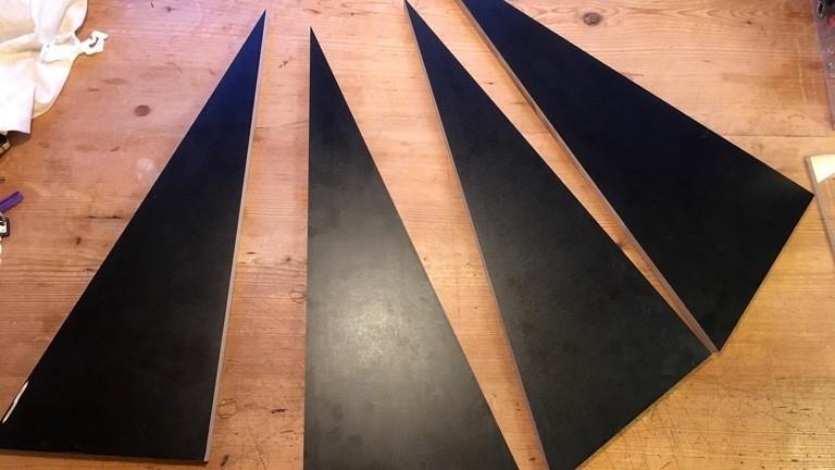 Schwarze dreieckige Multiplex-Platten liegen auf einem Holzfußboden.