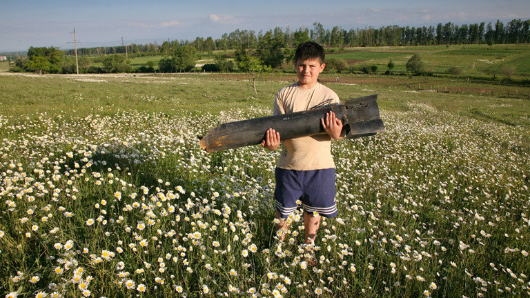 Junge mit einer explodierten Bombe auf einer Blumenwiese in Südossetien, Kaukasus, 25.06.2009.