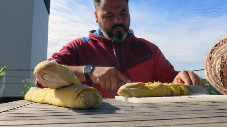 Brotsommelier Ralf Gießelmann schneidet das Mango-Curry-Baguette an.