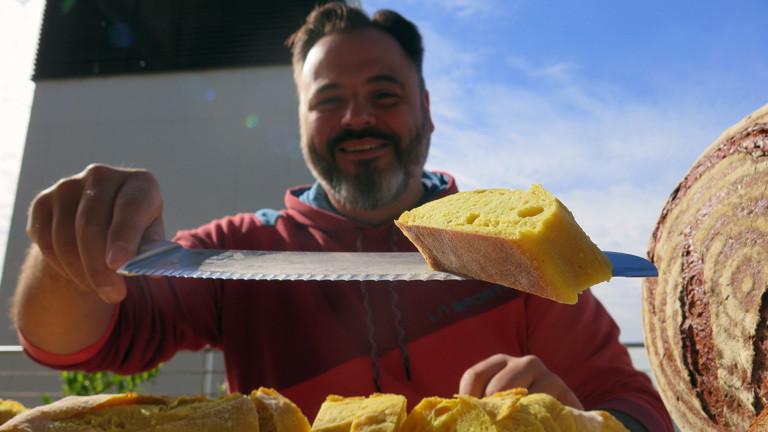 Brotsommelier Ralf Gießelmann bietet ein Stück vom Mango-Curry-Baguette an.