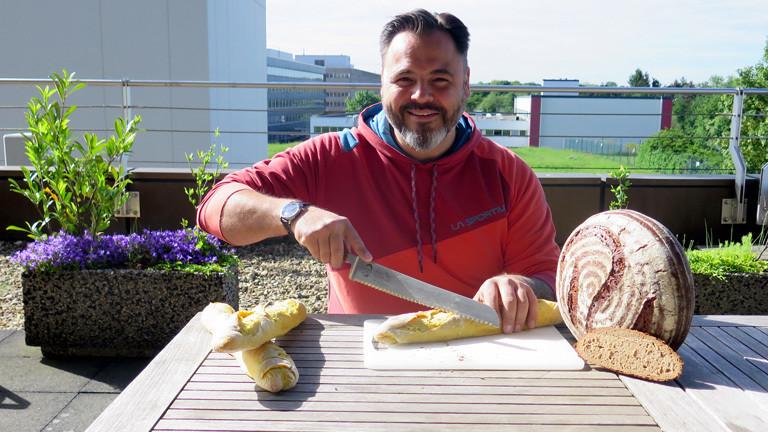 Brotsommelier Ralf Gießelmann schneidet das Mango-Curry Baguette an.