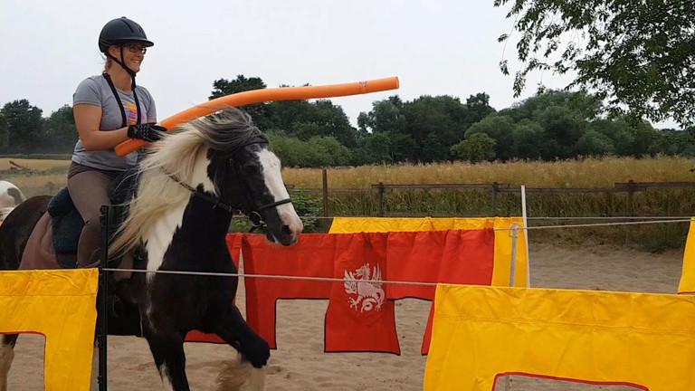 Caro Köhler auf einem Pferd bei einem Mittelalterturnier.