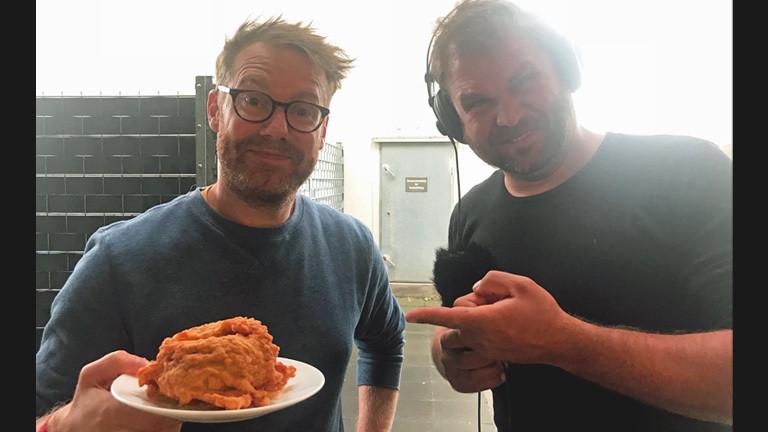 Christian Schmitt und Paulus Müller essen frittierten Burger