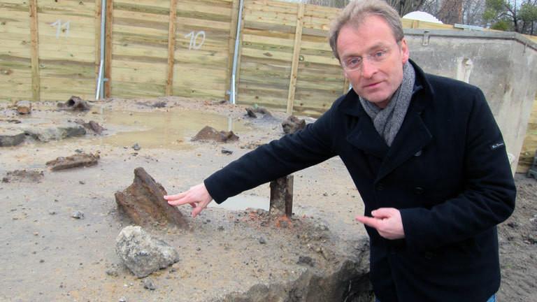 Torsten Dressler, Archäologe steht an einer Baustelle mit Resten der Berliner Mauer.
