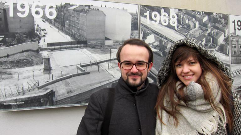 Anna und Sebastian aus Polen stehen vor Schwarz-Weiß-Bildern mit der Berliner Mauer.