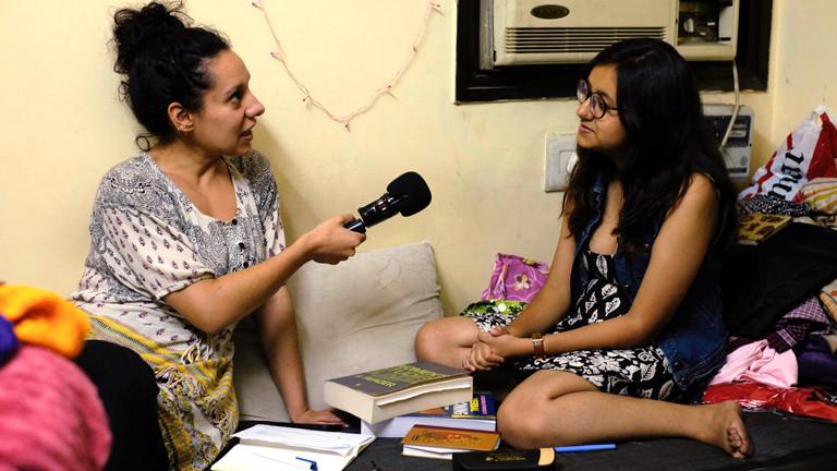 DRadio-Wissen-Reporterin Julia Wadhawan mit Ishani im Wohnzimmer des Studentenwohnheims