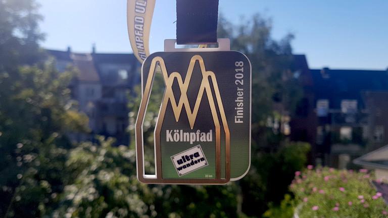 Reporterin Caro Köhler erhält eine Medaille nach einer vollbrachten Ultrawanderung.