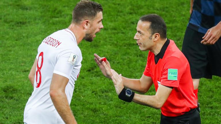 Englands Nationalspieler Jordan Henderson ist aufgebracht, Schiedsrichter Cuneyt Cakir beschwichtigt.