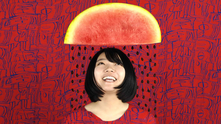 Eine Frau über deren Kopf eine Wassermelone zu schweben scheint.