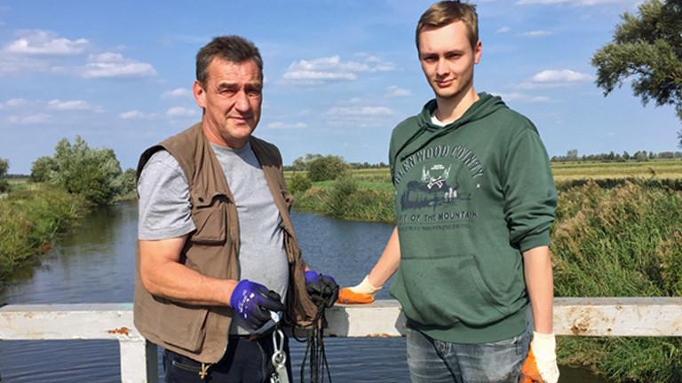 Magnetangler Wolfgang (60) und Lukas (24) auf einer Brücke in Schleswig-Holstein