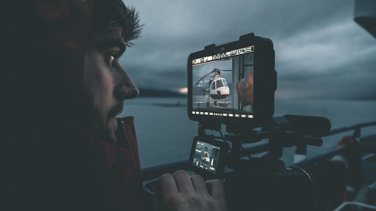 Dennis Vogt mit einer Kamera.