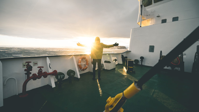 Ein Mann steht auf einem Schiff, das durch die Antarktis kreuzt.