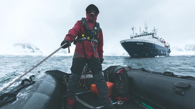 Ein Mann auf einem Schlauchboot. Im Hintergrund ein Forschungsschiff.