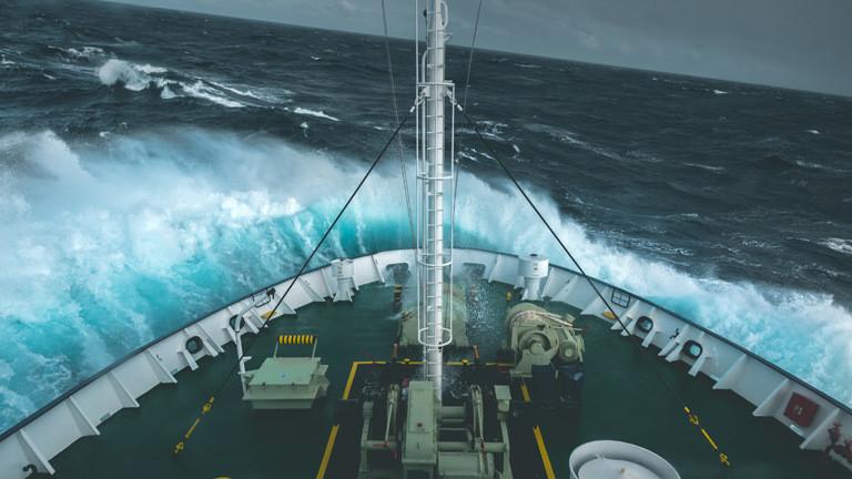Ein Schiff fährt durch hohe Wellen.