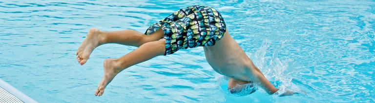 Mann springt in Pool.