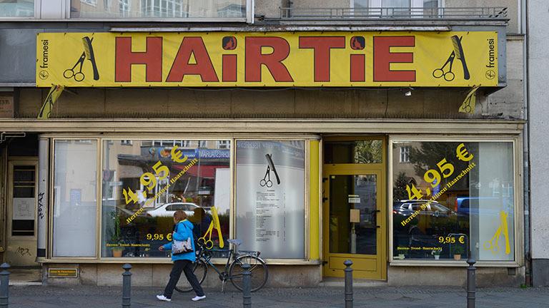 Ein Friseur wirbt mit Niedrigpreisen auf dem Schaufenster.