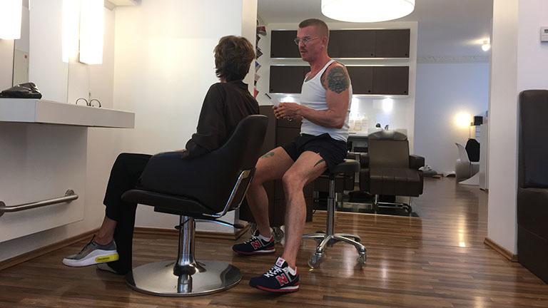 Eine Kundin lässt sich in einem Friseursalon von einem Friseur beraten.