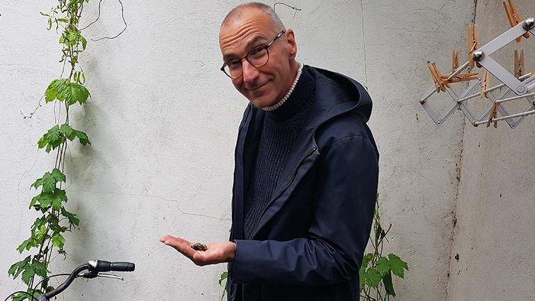 Evolutionsbiologe Menno Schilthuizen hält ein paar Schnecken in seiner Hand.