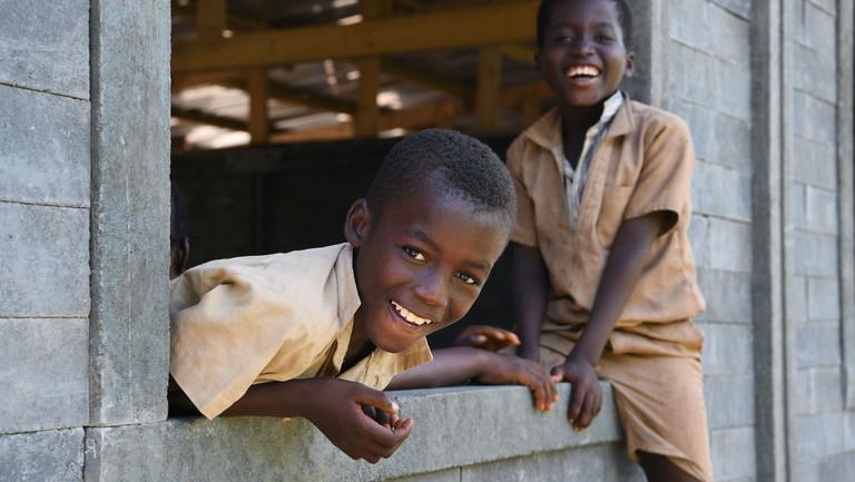Kinder gucken aus dem Bau ihrer neuen Klassen aus Plastikbausteinen in Sakassou, einem Dorf im Zentrum von Côte d'Ivoire in der Elfenbeinküste.