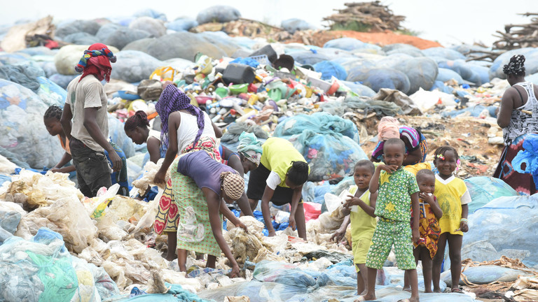 Frauen und Kinder sortieren Plastik auf einer Mülldeponie in Abidjan, der Hauptstadt der Elfenbeinküste.