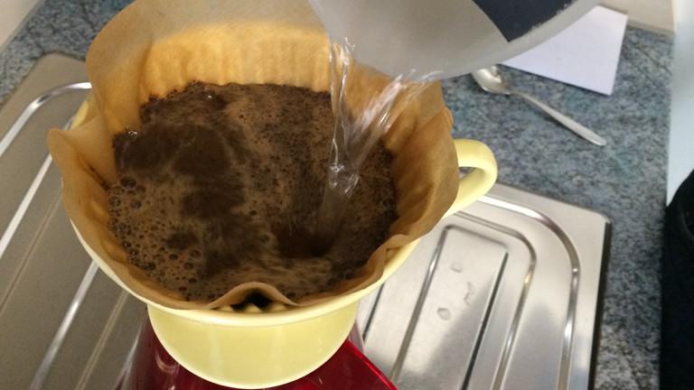 Heißes Wasser wird auf Kaffeepulver aufgegossen.