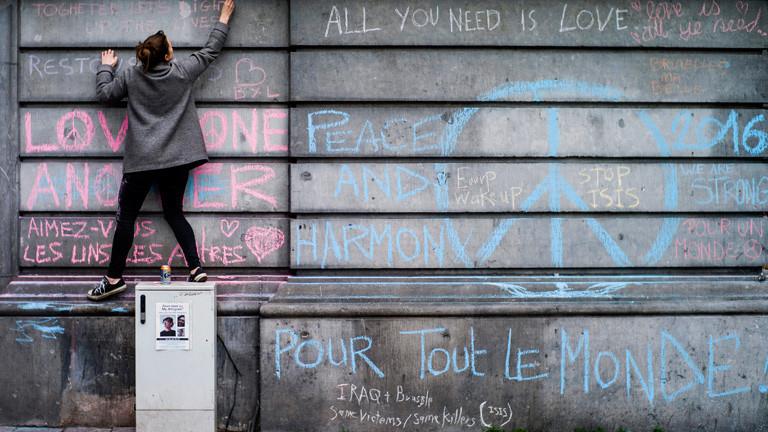 Eine junge Frau schreibt auf die Trauerwand an der Brüsseler Börse.