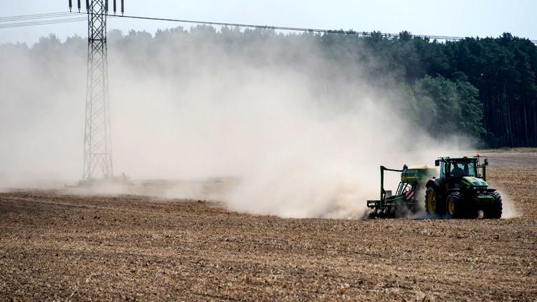Ein Traktor fährt über ein trockenes Feld und wirbelt Staub auf
