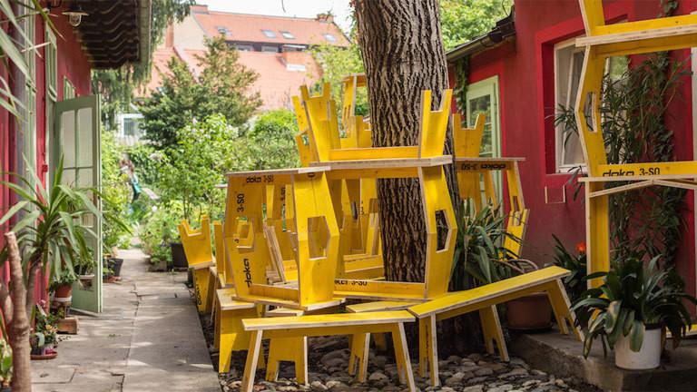 Mehrere gelbe Bänkchen rund um einen Baum aufgestapelt