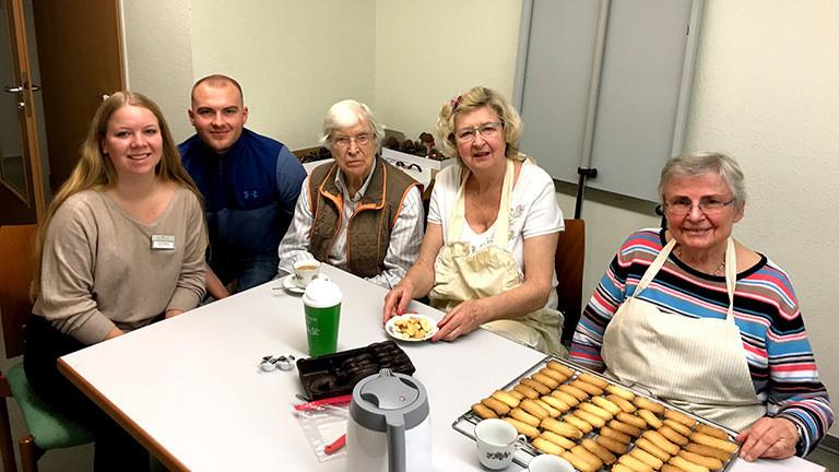Studenten und Senioren an einem Tisch mit Plätzchen