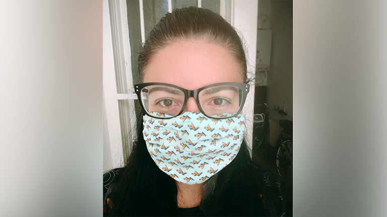 Eine Frau mit selbstgenähter Atemschutzmaske und Brille guckt in die Kamera.
