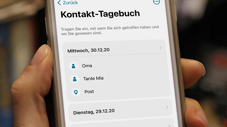 Eine Hand hält ein Handy, auf dem das Kontakt-Tagebuch der Corona-Warn-App geöffnet ist.