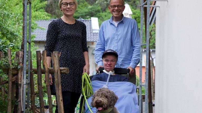 Benni ist mit seinen Eltern und ihrem Hund vor dem Haus.